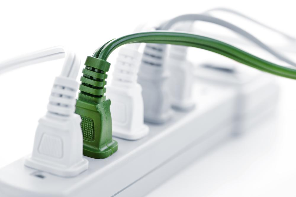 4 white and 1 green plugs in a power strip